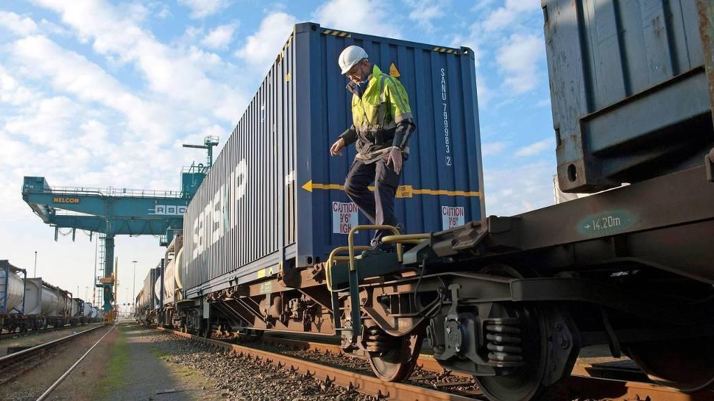 Waalhaven Rotterdam. Een medewerker van DB Schenker, een transportmaatschappij in de Rotterdamse haven controleert de sluitingen van de containers, de remmen van en de koppelingen tussen wagons van een goederentrein die op punt staat te vertrekken.