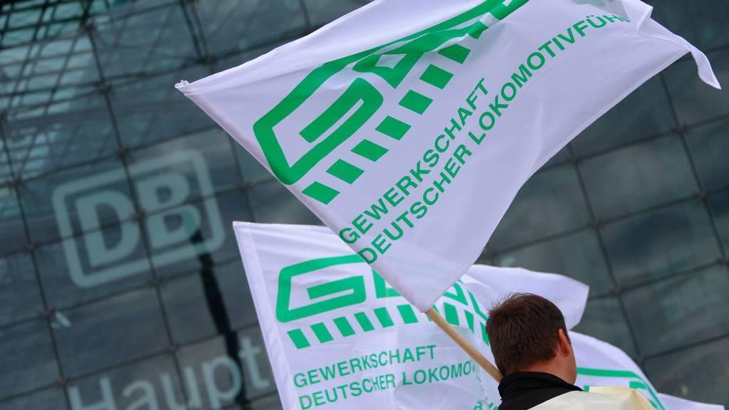 Stakende treinmachinisten met de vlag van hun vakbond GDL.