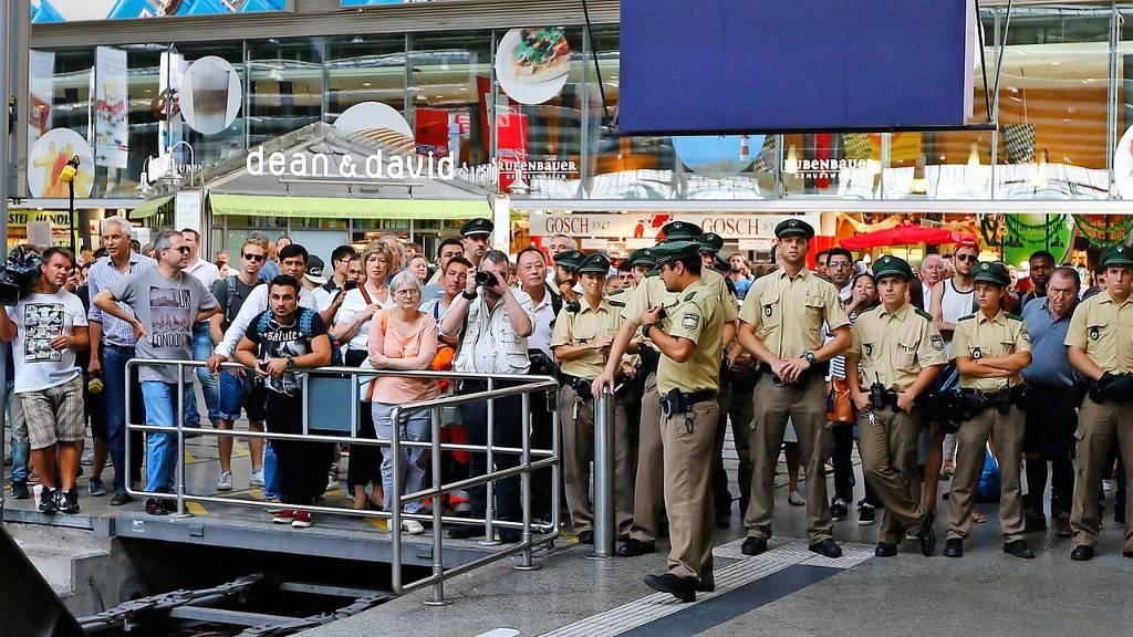 Politieagenten en belangstellenden wachten op het station van München op de vluchtelingen.