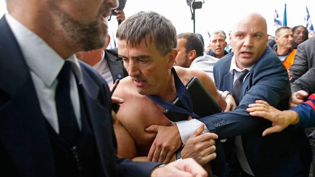 Zonder overhemd wordt Xavier Broseta, hoofd personeelszaken van Air France, wordt door beveiligers afgevoerd nadat actievoerder een vergadering op het hoofdkantoor van Air France hadden verstoord. Ze zijn boos over de plannen om 2900 banen te schrappen.