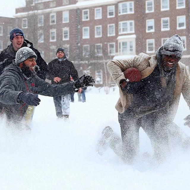 Studenten uit diverse landen spelen football in de sneeuw op de campus van Harvard University.