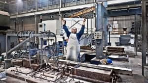 Medewerker van Brabant Alucast bezig met het vullen van de magnesiumoven waar hij bovenop staat. (HH)