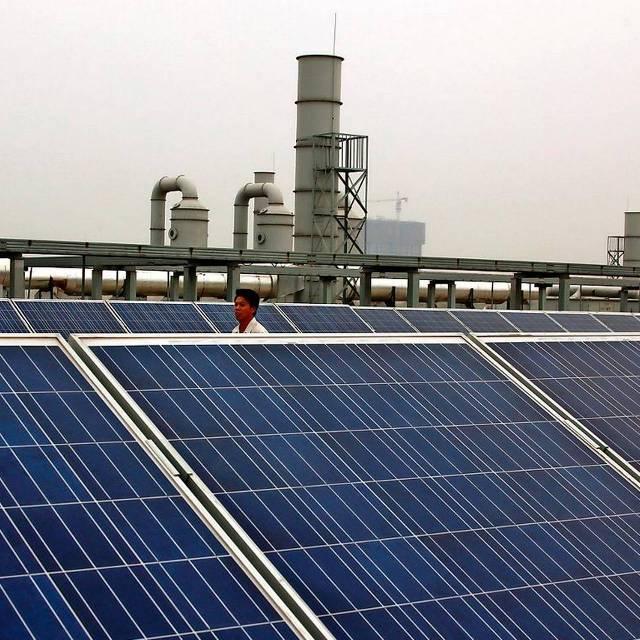 Een medewerker loopt over het dak van een Yingli Solar-fabriek. foto: Reuters