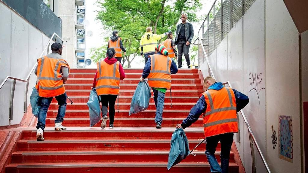 Rotterdamse uitkeringsgerechtigden verzamelen zwerfvuil. De havenstad weet de groei van de bijstand beter te beperken dan de drie andere grote steden. foto: HH