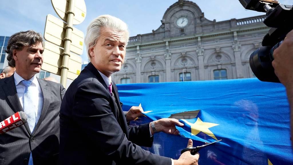 PVV-leider Geert Wilders knipt voor het Europees Parlement een ster uit de Europese vlag. Met deze daad benadrukte Wilders de anti-Europese houding van  zijn partij. Naast Wilders staat Marcel de Graaff, lijsttrekker voor de PVV bij de Europese parlementsverkiezingen van 2014.